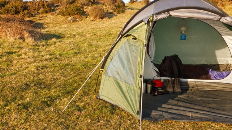 dome tent pitched in field for wild camping in the great outdoors with front flap open showing interior and copy space on left for text